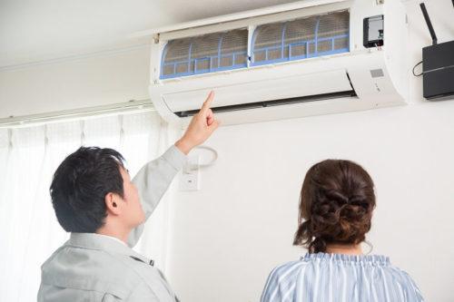 エアコンクリーニングを説明するクリーニング業者スタッフ