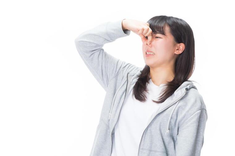 臭いに耐え切れず鼻をつまむ女性
