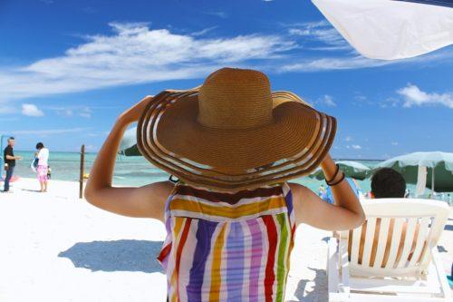 夏の海に臨む麦わら帽子の女性