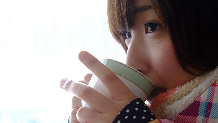 寒そうに暖かいコーヒーを飲む女性